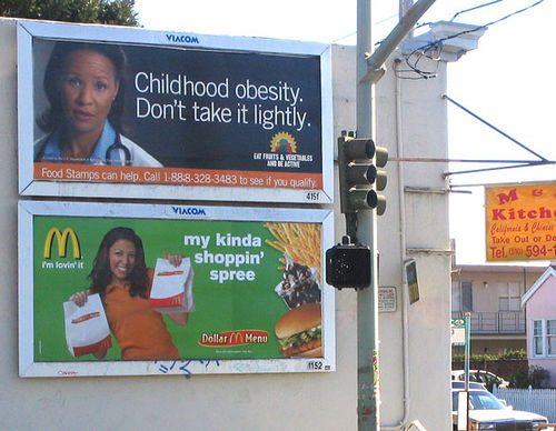 Advertisement placards on the street warning about the dangers of childhood obesity, and below an ad for McDonalds
